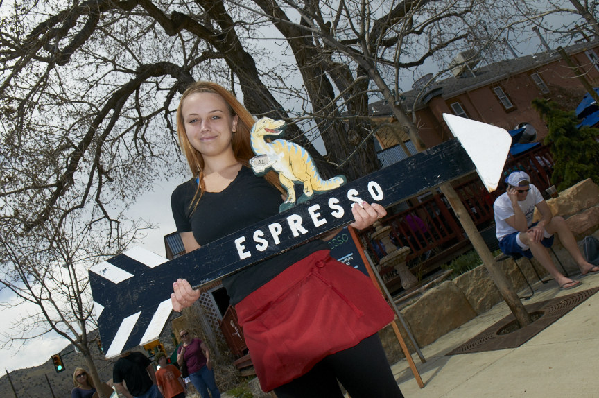 Photo of a woman holding a sign saying espresso.